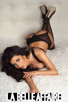 Sexy brunette woman lying in bed, wearing fashionable sensual black lingerie, looking at camera.