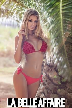 Beautiful sexy blonde woman posing in fashionable red swimsuit outdoor, looking at camera. Summer photo. Spain.