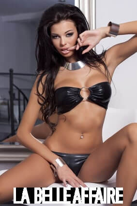 Sexy brunette woman posing in black lingerie and silver jewelry, looking at camera